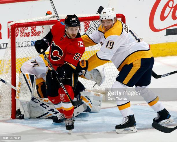 Andrew Mangiapane of the Calgary Flames and Calle Jarnkrok of the Nashville Predators battle for position during an NHL game on December 8, 2018 at...