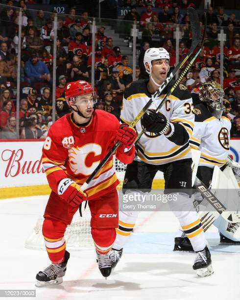 Andrew Mangiapane of the Calgary Flames and Charlie Coyle of the Boston Bruins skate during an NHL game on February 21, 2020 at the Scotiabank...