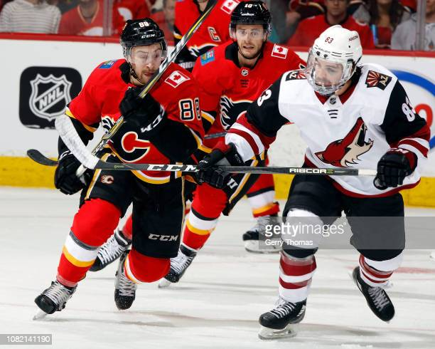 Andrew Mangiapane of the Calgary Flames and Conor Garland of the Arizona Coyotes skate during an NHL game on January 13 2019 at the Scotiabank...