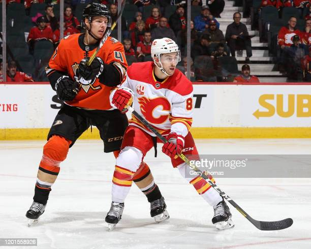 Andrew Mangiapane of the Calgary Flames and Hampus Lindholm of the Anaheim Ducks skate during an NHL game on February 17 2020 at the Scotiabank...