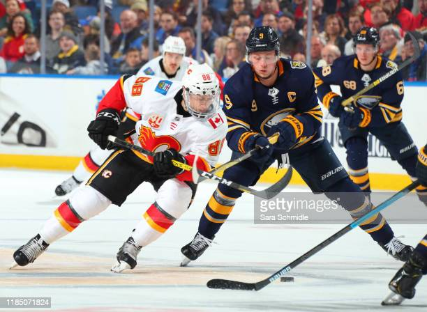 Andrew Mangiapane of the Calgary Flames and Jack Eichel of the Buffalo Sabres battle for the puck during an NHL game on November 27, 2019 at KeyBank...