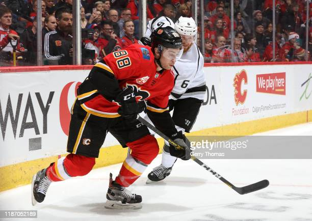Andrew Mangiapane of the Calgary Flames battles against Joakim Ryan of the Los Angeles Kings at Scotiabank Saddledome on December 7, 2019 in Calgary,...