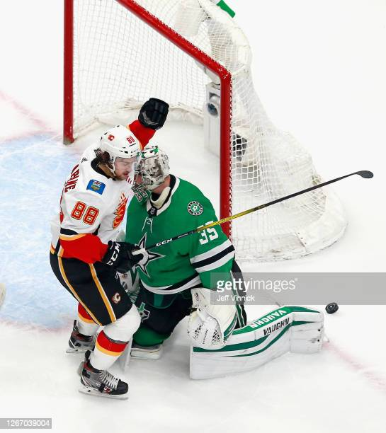 Andrew Mangiapane of the Calgary Flames celebrate a goal by Mikael Backlund against Anton Khudobin of the Dallas Stars at 19:14 of the first period...