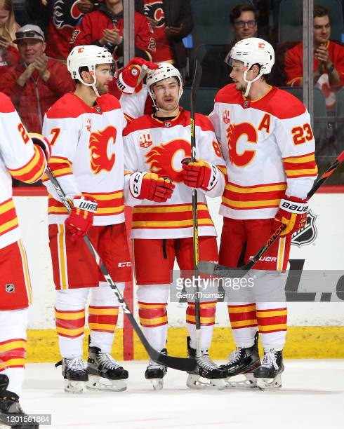 Andrew Mangiapane of the Calgary Flames celebrates his third goal against the Anaheim Ducks with Sean Monahan and TJ Brodie of the Calgary Flames...