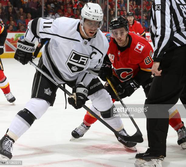 Andrew Mangiapane of the Calgary Flames faces off against Anze Kopitar of the Los Angeles Kings at Scotiabank Saddledome on December 7, 2019 in...