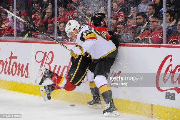 Andrew Mangiapane of the Calgary Flames flies into the boards after missing a check on Jonathan Marchessault of the Vegas Golden Knights during an...