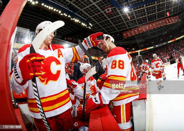 Andrew Mangiapane of the Calgary Flames is congratulated by Matthew Tkachuk of the Calgary Flames after scoring his third goal of the game against...