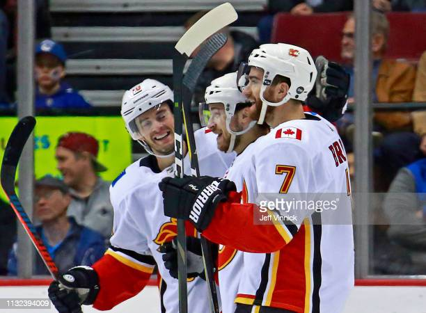 Andrew Mangiapane of the Calgary Flames is congratulated by teammates TJ Brodie and Derek Ryan after scoring during their NHL game against the...