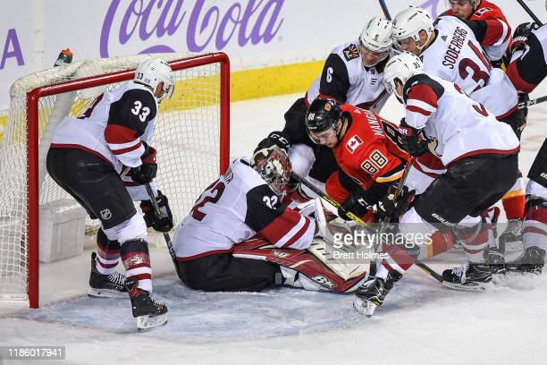 Andrew Mangiapane of the Calgary Flames is surrounded by Arizona Coyotes players as he looks for the puck during an NHL game on November 5, 2019 at...