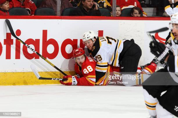 Andrew Mangiapane of the Calgary Flames is taken down by Jeremy Lauzon of the Boston Bruins during an NHL game on February 21, 2020 at the Scotiabank...