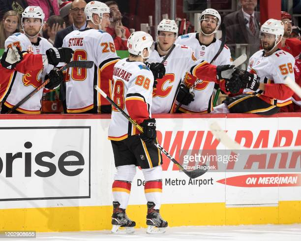 Andrew Mangiapane of the Calgary Flames pounds gloves with teammates on the bench following his second period goal during an NHL game against the...