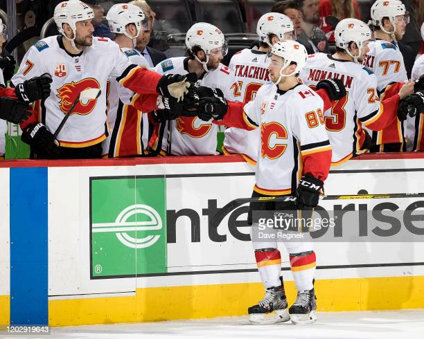 Andrew Mangiapane of the Calgary Flames pounds gloves with teammates on the bench following his third period goal during an NHL game against the...