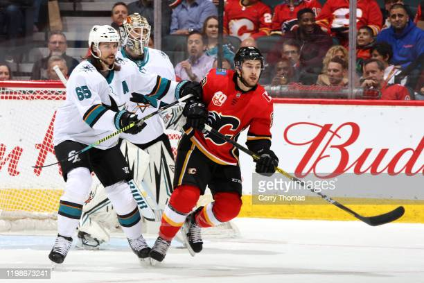 Andrew Mangiapane of the Calgary Flames skates against Erik Karlsson of the San Jose Sharks at Scotiabank Saddledome on February 04, 2020 in Calgary,...