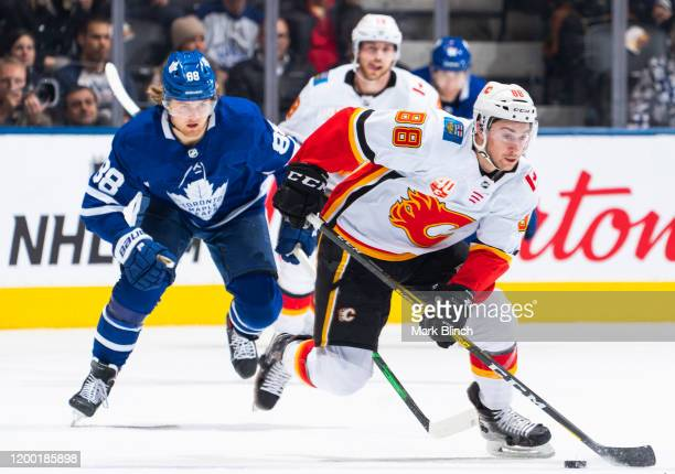 Andrew Mangiapane of the Calgary Flames skates against William Nylander of the Toronto Maple Leafs during the second period at the Scotiabank Arena...