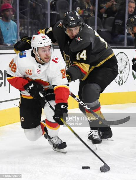 Andrew Mangiapane of the Calgary Flames tries to control the puck under pressure from Nicolas Hague of the Vegas Golden Knights in the third period...