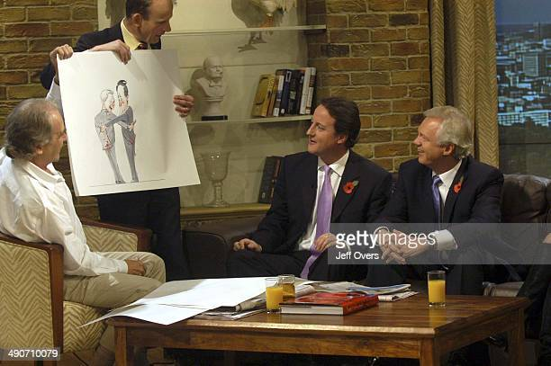 Andrew Marr holds up a cartoon by the seated Gerald Scarfe which shows David Cameron and David Davis Both the Conservative Party leadership...