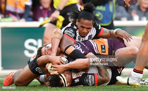 Andrew McCullough of the Broncos is held up over the line by the Warriors defence during the round 18 NRL match between the Brisbane Broncos and the...