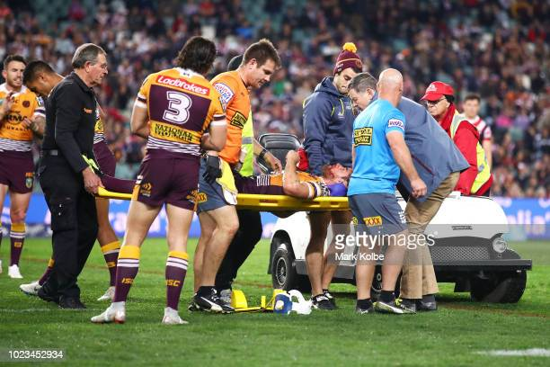 Andrew McCullough of the Broncos is stretchered from the field after a tackle from Dylan Napa of the Roosters during the round 24 NRL match between...