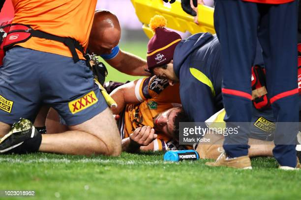 Andrew McCullough of the Broncos receives attention from the trainers as he lies injured on the ground after a tackle by Dylan Napa of the Roosters...