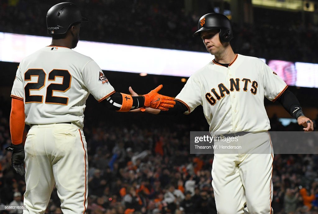 Andrew McCutchen #22 and Buster Posey #28 of the San Francisco Giants congratulate each other after they both scored on a two-run rbi double from Brandon Belt #9 against the Cincinnati Reds in the bottom of the six inning at AT&T Park on May 14, 2018 in San Francisco, California.