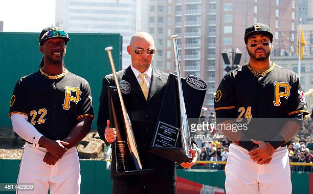 Andrew McCutchen and Pedro Alvarez of the Pittsburgh Pirates stand stand with former Pirate Jack Wilson to receive their National League Silver...