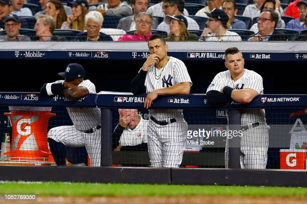 Andrew McCutchen Giancarlo Stanton and Luke Voit of the New York Yankees looks on from the dugout against the Boston Red Sox in Game Four of the...