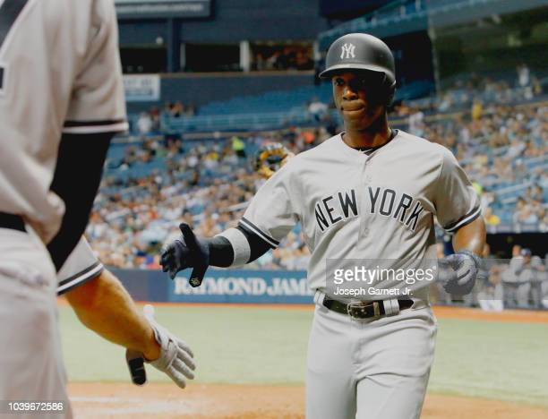 Andrew McCutchen of the New York Yankees prepares to shake a teammates hand after scoring his second run in the seventh inning of the game against...