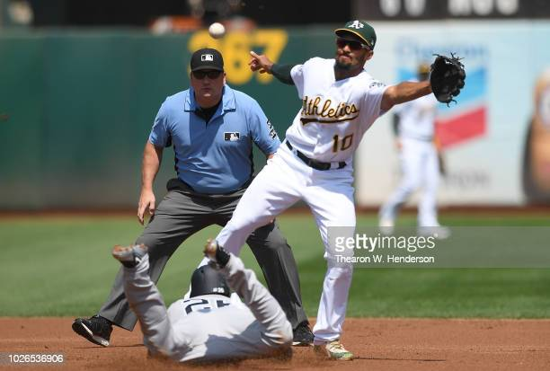 Andrew McCutchen of the New York Yankees steals second base as the ball is thrown past Marcus Semien of the Oakland Athletics in the top of the first...