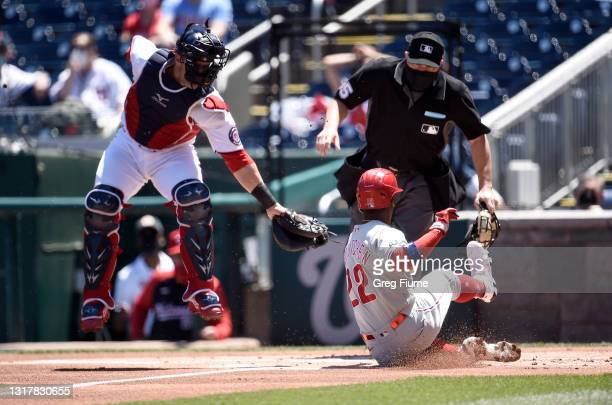 Andrew McCutchen of the Philadelphia Phillies scores in the first inning ahead of the tag of Yan Gomes of the Washington Nationals at Nationals Park...