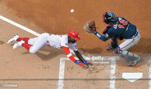 Andrew McCutchen of the Philadelphia Phillies slides into home to score a run in the first inning as Travis d'Arnaud of the Atlanta Braves catches...