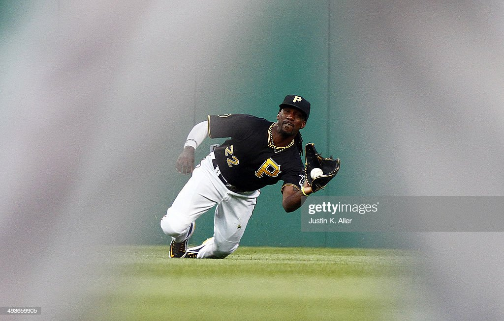 Andrew McCutchen #22 of the Pittsburgh Pirates attempts to make a diving catch in the fourth inning against the Washington Nationals during the game at PNC Park May 24, 2014 in Pittsburgh, Pennsylvania.