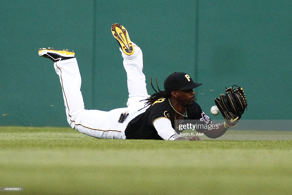 Andrew McCutchen #22 of the Pittsburgh Pirates can't hold on to the ball in the fourth inning attempting to make a catch against the Washington Nationals during the game at PNC Park May 24, 2014 in Pittsburgh, Pennsylvania.