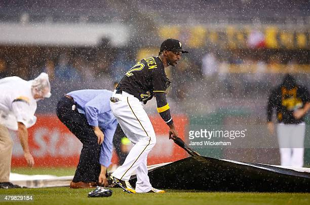 Andrew McCutchen of the Pittsburgh Pirates helps out members of the grounds crew by holding down the tarp as heavy wind and rain started in the third...