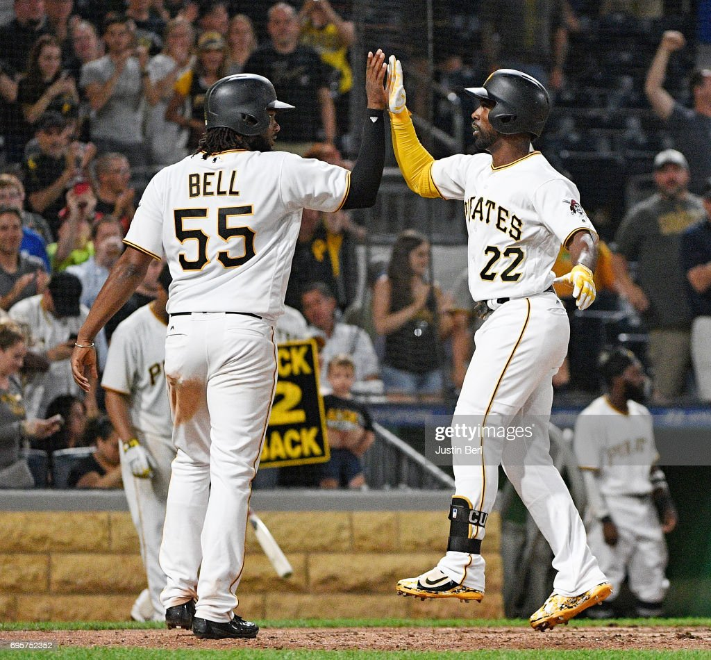 Andrew McCutchen #22 of the Pittsburgh Pirates high fives with Josh Bell #55 after hitting a two run home run in the eighth inning during the game against the Colorado Rockies at PNC Park on June 13, 2017 in Pittsburgh, Pennsylvania.
