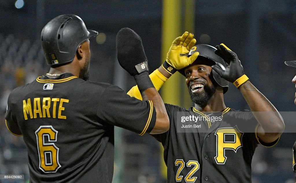 Andrew McCutchen #22 of the Pittsburgh Pirates high fives with Starling Marte #6 after hitting a three run home run in the sixth inning during the game against the Baltimore Orioles at PNC Park on September 26, 2017 in Pittsburgh, Pennsylvania.