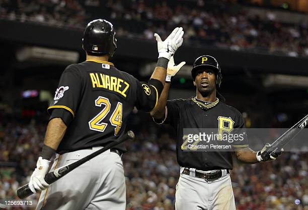 Andrew McCutchen of the Pittsburgh Pirates highfives Pedro Alvarez after scoring against the Arizona Diamondbacks during the fifth inning of the...