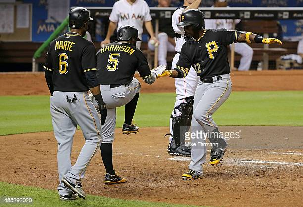 Andrew McCutchen of the Pittsburgh Pirates is congratulated by Josh Harrison and Starling Marte after hitting a three run home run during a game...