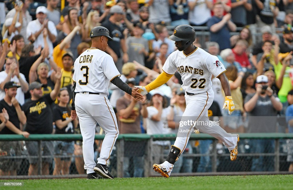 Andrew McCutchen #22 of the Pittsburgh Pirates is greeted by third base coach Joey Cora #3 as he rounds the bases after hitting a solo home run in the fourth inning during the game against the Colorado Rockies at PNC Park on June 13, 2017 in Pittsburgh, Pennsylvania.