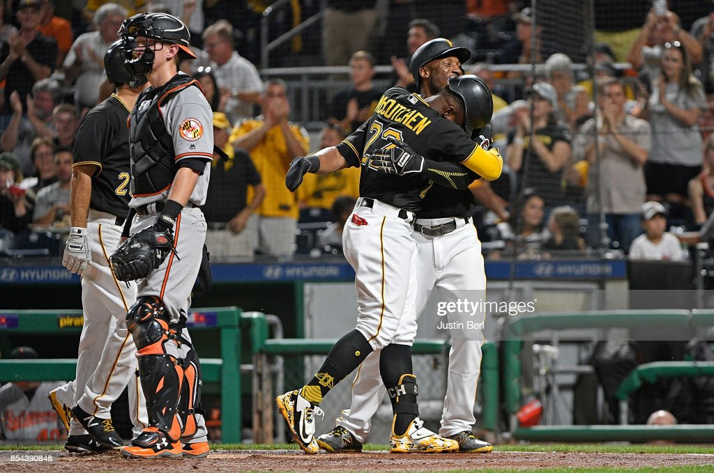 Andrew McCutchen #22 of the Pittsburgh Pirates is hugged by Starling Marte #6 as he crosses home plate after hitting a grand slam home run in the second inning during the game against the Baltimore Orioles at PNC Park on September 26, 2017 in Pittsburgh, Pennsylvania. The grand slam home run was the first of McCutchen's career.