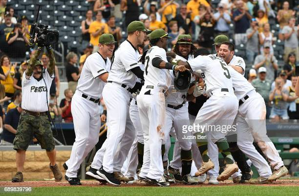Andrew McCutchen of the Pittsburgh Pirates is mobbed by teammates at home plate after hitting a walk off home run in the ninth inning to give the...