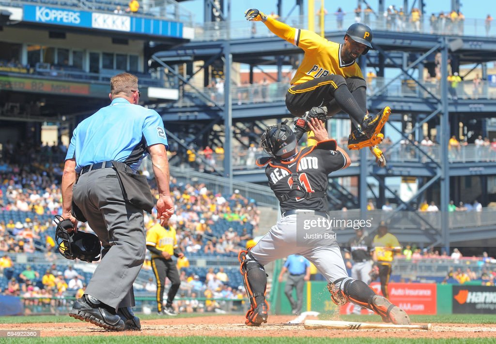Andrew McCutchen #22 of the Pittsburgh Pirates is tagged out at home plate by J.T. Realmuto #11 of the Miami Marlins as part of a double play in the sixth inning during the game PNC Park on June 11, 2017 in Pittsburgh, Pennsylvania.