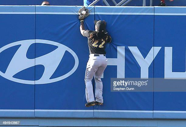 Andrew McCutchen of the Pittsburgh Pirates jumps at the wall but can't catch a two run triple hit by Drew Butera of the Los Angeles Dodgers in the...