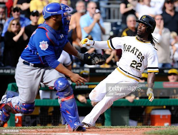 Andrew McCutchen of the Pittsburgh Pirates scores in front of Welington Castillo of the Chicago Cubs during the eighth inning on September 15 2013 at...