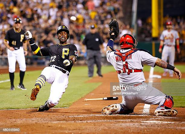 Andrew McCutchen of the Pittsburgh Pirates scores safely in the 8th inning past Yadier Molina of the St Louis Cardinals during the game at PNC Park...