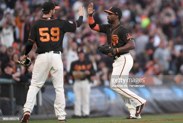 Andrew McCutchen of the San Francisco Giants gets a highfive from starting pitcher Andrew Suarez after McCutchen ran down a deep fly ball in right...