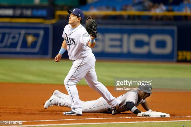 Andrew McCutchen of the Yankees dives safely back into first base as Rays first baseman JiMan Choi reaches for the pick off throw during the MLB...