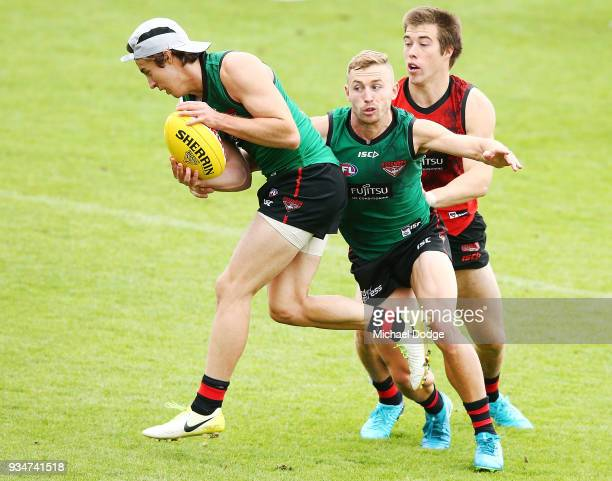 Andrew MGrath is tackled by Devon Smith and Zach Merrett during an Essendon Bombers AFL training session at The Hangar on March 20 2018 in Melbourne...