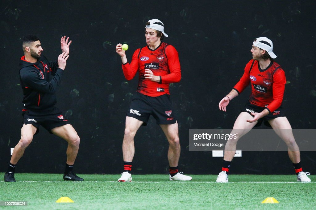 Andrew MGrath of the Bombers catches a tennis ball when taking part in a reflex drill with Adam Saad (L) and Travis Colyer during an Essendon Bombers AFL training session at The Hangar on July 30, 2018 in Melbourne, Australia.