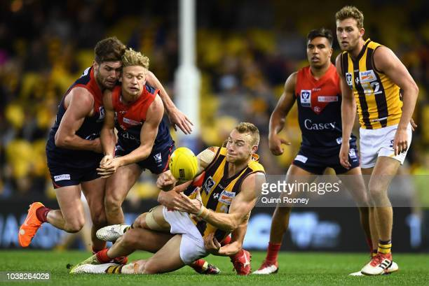 Andrew Moore of Box Hill handballs whilst being tackled during the VFL Grand Final match between Casey and Box Hill at Etihad Stadium on September 23...
