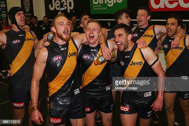 Andrew Moore of the Tigers Nathan Drummond and Adam Marcon sing the club song after winning during the round 20 AFL match between the Richmond Tigers...